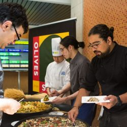 two chefs serving some food to a person