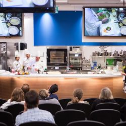 view from a seat looking at students prepare a meal on stage