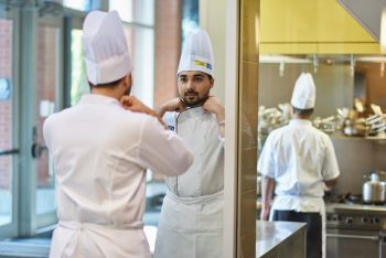 a chef fixing his outfit in front of a mirror