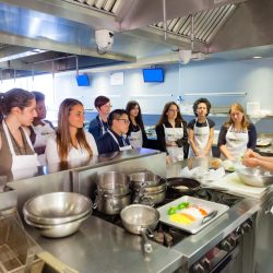 Attendees watching the chef during a kitchen demonstration